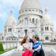 Stock Photo: Couple of tourists sitting by the Sacre-Coeur in Paris