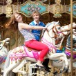 Cheerful young couple enjyong their ride on merry-go-round - Stock Photo