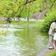 Happy just married couple hugging and kissing near the lake in p — Stock Photo #12014707