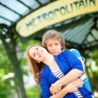 Young beautiful couple in Paris at the entrance to metro station — Stock Photo