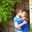 Young loving couple kissing by the door — Stock Photo