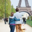 Young couple going to have a picnic by the Eiffel Tower - Stock Photo