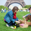 Young couple having a picnic near the Eiffel tower — Stock Photo