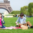 Stock Photo: Young couple having a picnic near the Eiffel tower