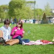 Happy young couple having a picnic and making bubbles — Stock Photo