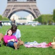 Young couple having a picnic near the Eiffel tower — Stock Photo #12019317