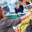 Beutiful woman buying grapes at market — Stock Photo