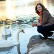 Happy beautiful girl in Paris feeding swans — Stock Photo