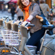 Beautiful girl with baguttes taking a bike for rent in Paris — Stock Photo