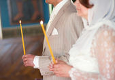 Couple in a church during wedding ceremony, holding candles — Stock Photo