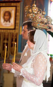 Bride and groom during orthodox wedding ceremony with candles an — Stock Photo