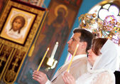 Bride and groom during orthodox wedding ceremony with crowns abo — Stock Photo