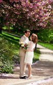 Bride and groom in park at springtime — Stock Photo