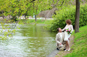 Happy just married couple hugging near the water in park — Stock Photo