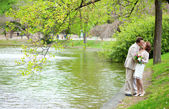 Happy just married couple hugging and kissing near the lake in p — Stock Photo