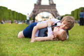 Laughing couple lying on the grass near the Eiffel Tower — Stock Photo