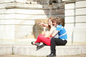 Joyful couple sitting by the fountain and looking at something — Stock Photo