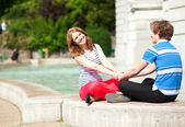 Young happy couple sitting near water and holding hands — Stock Photo