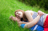 Romantic couple lying on the grass and hugging — Stock Photo