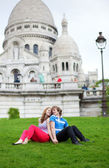Couple of tourists sitting on the grass by the Sacre-Coeur — Stock Photo