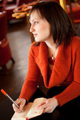Beautiful young woman writing something in her personal organize — Stock Photo