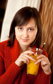Beautiful young woman with orange juice in a cafe — Stock Photo
