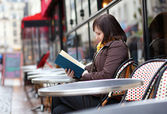 Beautiful young girl reading a book in Parisian street cafe — Stock Photo