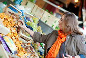 Beautiful woman buying mushrooms at market — Stock Photo