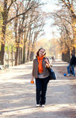 Beautiful young woman with orange in park at fall — Stock Photo