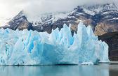 Blauwe ijsbergen en besneeuwde bergen op grijs glacier in torres del — Stockfoto