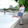 Happy romantic couple is hugging near the Seine, girl is jumping — Stock Photo #12843800