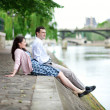 Joyful couple is sitting on the embankment — Stock Photo