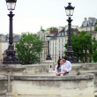 Dating couple is kissing gently in Paris on a bridge — Stock Photo