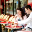 Happy couple drinking coffee in a Parisian outdoor cafe — Stock Photo