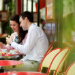 Happy couple eating macaroons in a Parisian outdoor cafe — Stock Photo #12843943