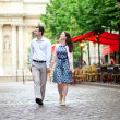 Couple walking in Paris near a street cafe — Stock Photo
