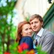 Man and woman together on balcony with blossoming geranium — Stock Photo #12844433