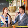 Beautiful couple drinking red wine in a French cafe — Stockfoto