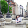 Stock Photo: Dating couple is kissing tenderly in Paris on a bridge