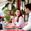 happy couple drinking coffee or tea in a parisian outdoor cafe — Stock Photo
