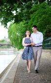 Happy positive couple is walking together by the Seine — Stock Photo