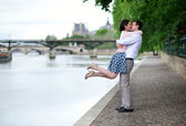 Happy romantic couple is hugging near the Seine, girl is jumping — Stock Photo