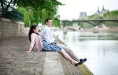 Joyful couple is sitting on the embankment — Stock Photo