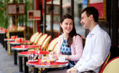 Happy couple in a Parisian outdoor cafe — Stock Photo