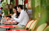 Happy couple eating macaroons in a Parisian outdoor cafe — Stock Photo