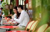 Pareja feliz comiendo macarrones en un café parisino al aire libre — Foto de Stock
