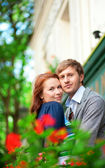 Man and woman together on balcony with blossoming geranium — Stock Photo