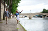 Couple is walking by the Seine embankment in Paris, girl is bala — Stock Photo