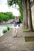 Positive laughing couple is dancing on the Seine embankment in P — Stock Photo