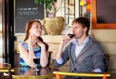 Beautiful couple drinking red wine in a French cafe — Stock Photo